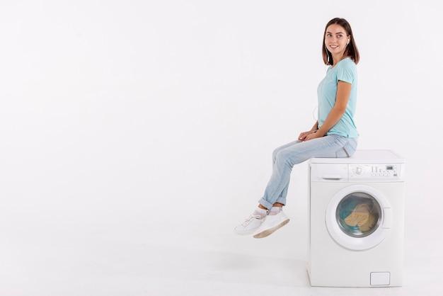 Donna della foto a figura intera che posa sulla lavatrice