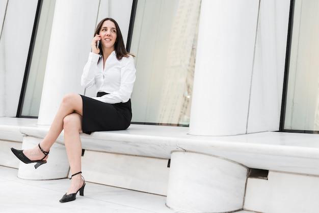 Donna della foto a figura intera che si siede con il telefono