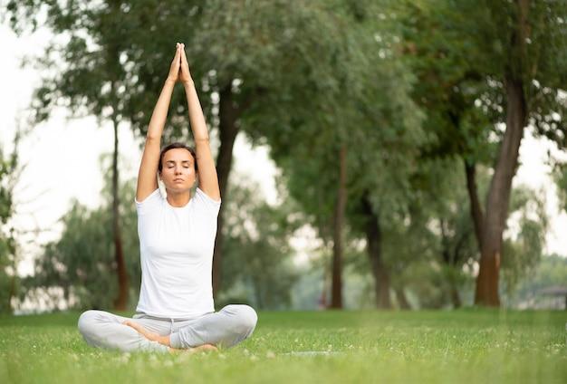 Donna della foto a figura intera che si siede e che medita