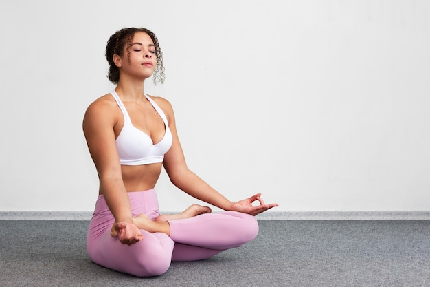 Donna della foto a figura intera che si siede nella posizione meditating