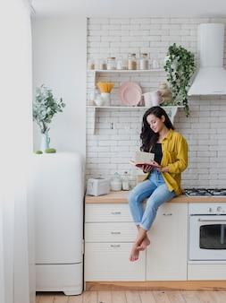 Donna della foto a figura intera che si siede sul controsoffitto della cucina