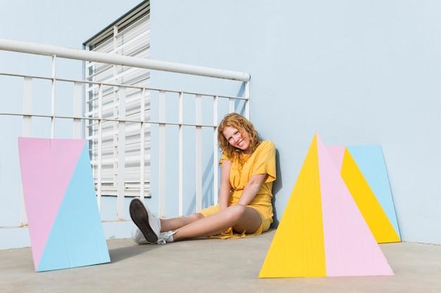 Donna della foto a figura intera che si siede sul pavimento