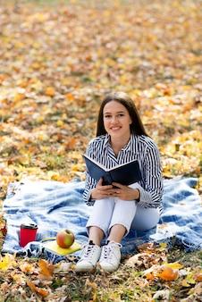 Donna della foto a figura intera che tiene un libro