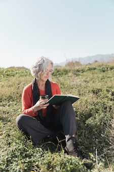 Donna della foto a figura intera con caffè e libro all'aperto