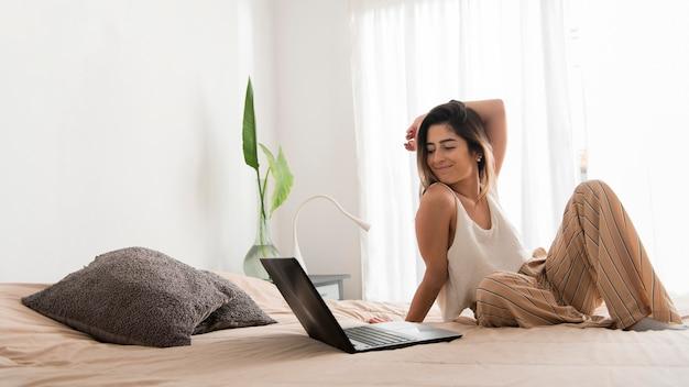 Donna della foto a figura intera con il computer portatile a letto