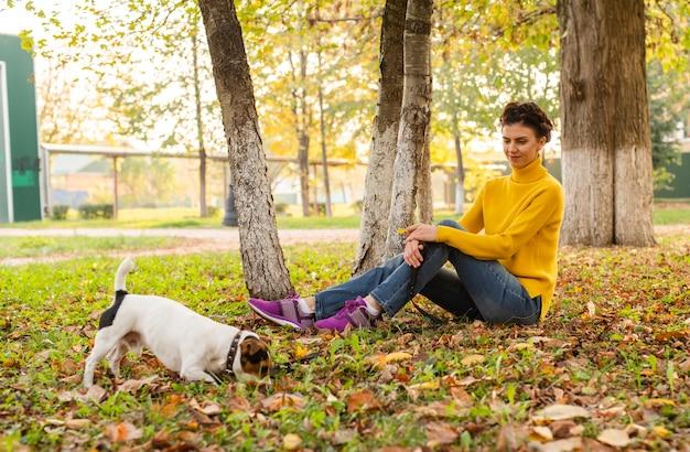 Donna della foto a figura intera con il suo cane nel parco