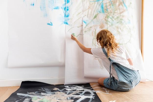 Donna della foto a figura intera con la bottiglia della vernice