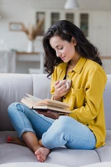 Donna della foto a figura intera con la tazza e il libro