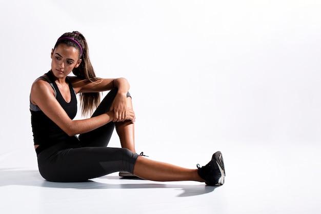 Donna della foto a figura intera nella seduta del vestito di ginnastica