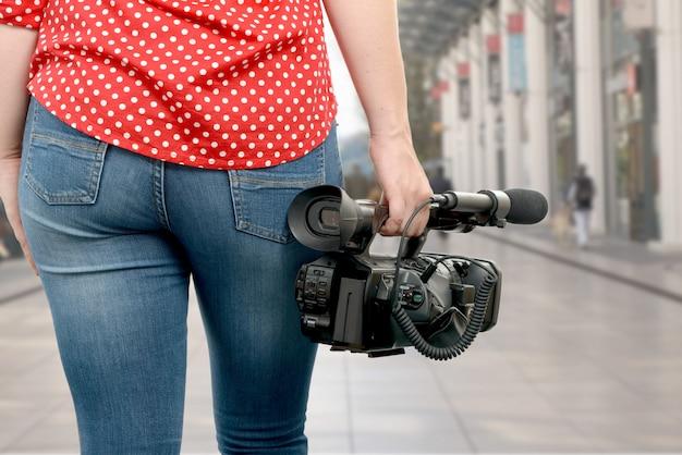 Donna della macchina fotografica che tiene la sua videocamera professionale nella via
