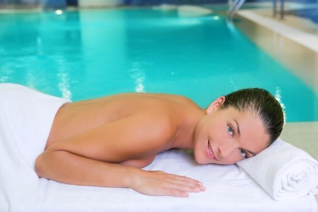 Donna della piscina della stazione termale distesa sull'asciugamano bianco