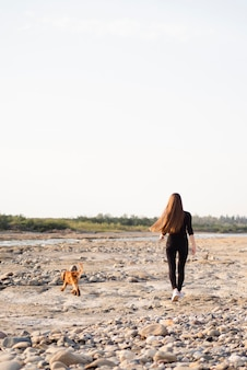Donna della possibilità remota che cammina con il suo cane