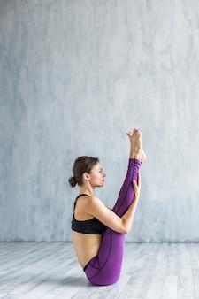 Donna della possibilità remota che si siede in una posizione di yoga