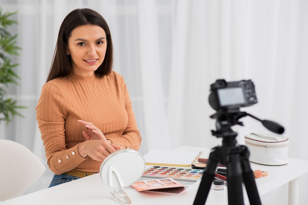 Donna della registrazione della macchina fotografica mentre provando trucco