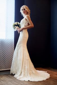 Donna della sposa di mattina in un abito da sposa bianco