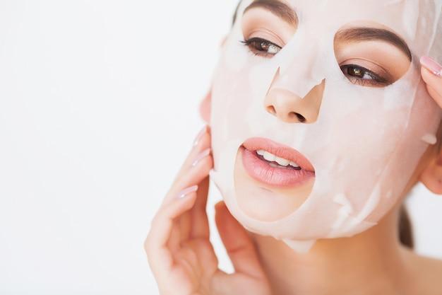 Donna della stazione termale che applica maschera detergente viso, trattamenti di bellezza