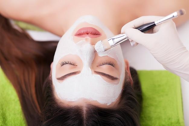 Donna della stazione termale che applica maschera di pulizia facciale. trattamenti di bellezza. maschera di argilla