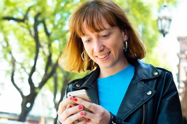 Donna della testarossa che invia messaggio con lo smartphone.