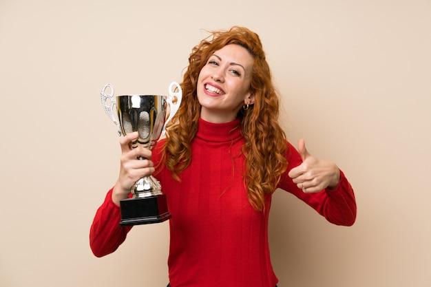 Donna della testarossa con il maglione del collo alto che tiene un trofeo