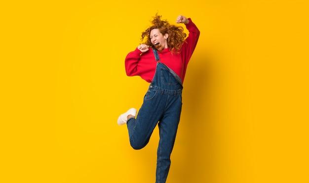 Donna della testarossa con la tuta che salta sopra la parete gialla isolata