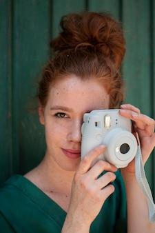 Donna della testarossa del primo piano che per mezzo di una macchina fotografica d'annata