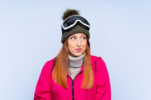 Donna della testarossa dello sciatore con i vetri di snowboard sopra la parete blu isolata che sta e che guarda al lato