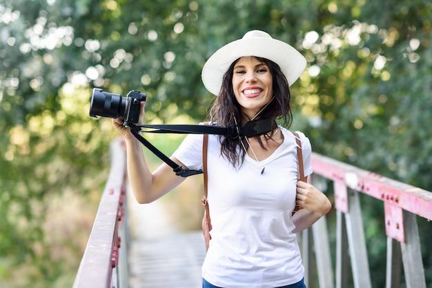 Donna della viandante che prende le fotografie con una macchina fotografica mirrorless