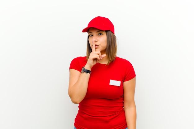 Donna delle consegne che chiede silenzio e silenzio, gesticolando con un dito davanti alla bocca, dicendo shh o mantenendo un segreto