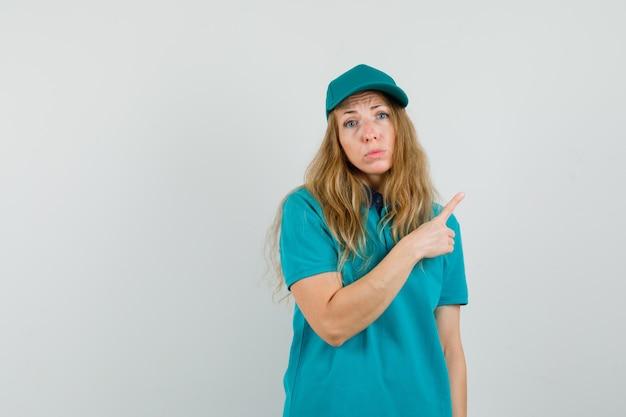 Donna delle consegne che punta lontano in t-shirt, berretto e sembra senza speranza.