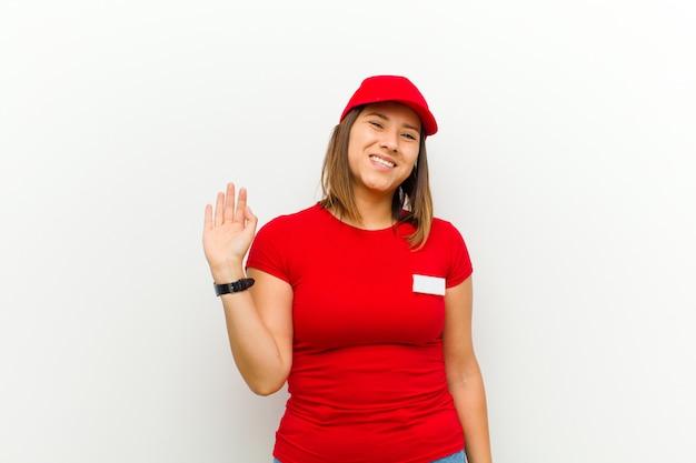 Donna delle consegne che sorride allegramente e allegramente, agitando la mano, dandoti il benvenuto e salutandoti, o salutandoti