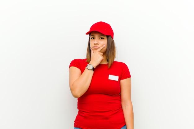 Donna delle consegne dall'aspetto serio, riflessivo e diffidente, con un braccio incrociato e la mano sul mento, opzioni di ponderazione