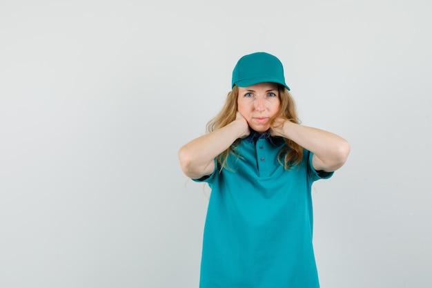 Donna delle consegne in t-shirt, berretto tenendo le mani sul collo e guardando pensieroso