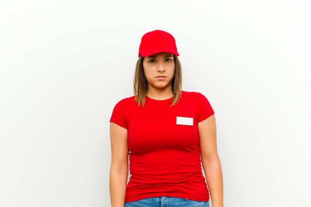 Donna delle consegne sentirsi triste, arrabbiata o arrabbiata e guardando di lato con un atteggiamento negativo, accigliata in disaccordo contro il bianco