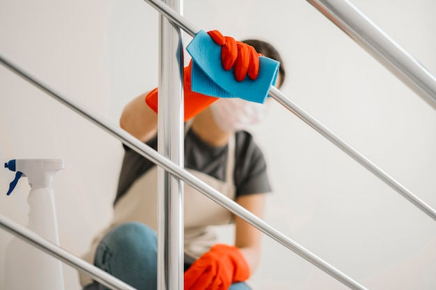 Donna delle pulizie che indossa una maschera