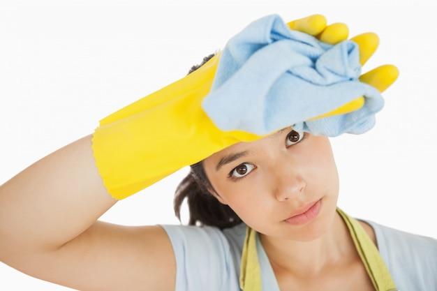 Donna delle pulizie che si asciuga la fronte