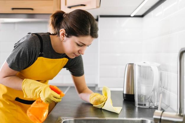 Donna delle pulizie di colpo medio della cucina