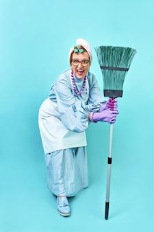 Donna delle pulizie divertente casalinga divertente anziana che scherza con una scopa.