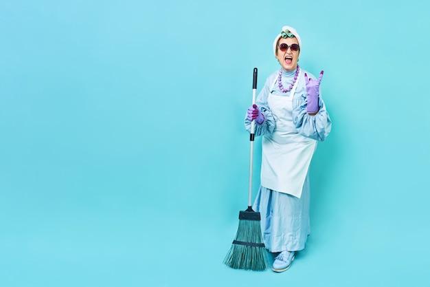 Donna delle pulizie divertente casalinga funky anziana che scherza con una scopa.