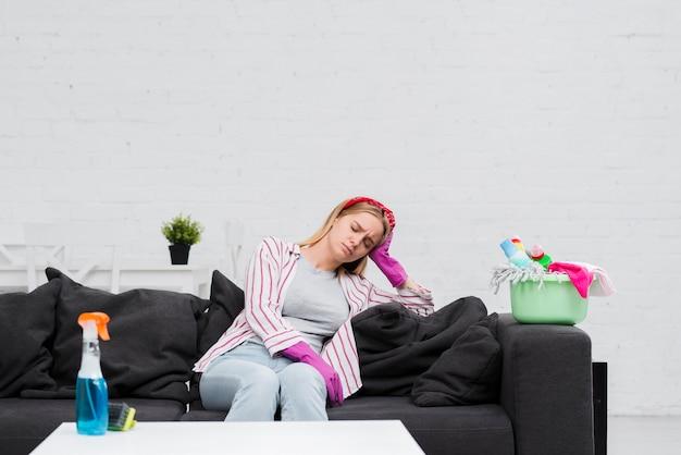Donna delle pulizie in pausa seduto sul divano