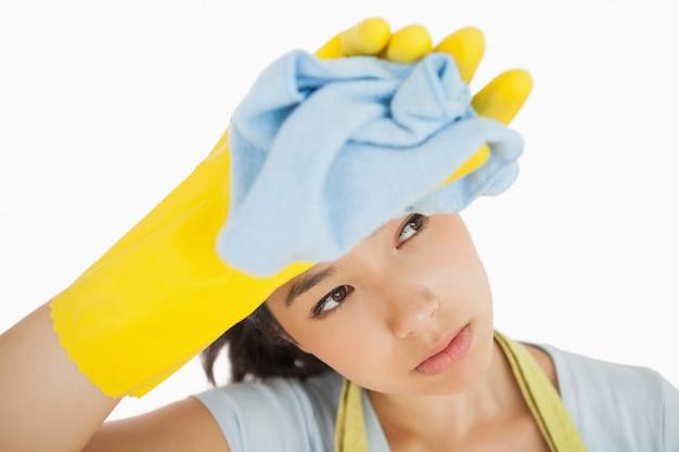 Donna delle pulizie oberati di lavoro asciugandosi la fronte