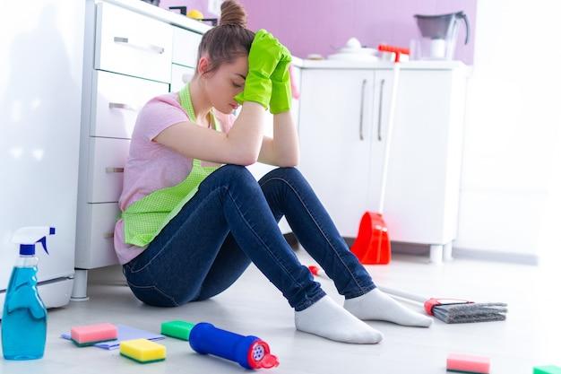Donna delle pulizie sovraccarica stanca che sente affaticamento della giornata indaffarata e che pulisce casa alla cucina a casa