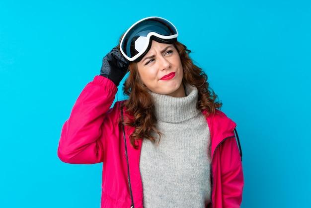 Donna dello sciatore con i vetri di snowboard sopra la parete blu isolata che ha dubbi e con l'espressione confusa del fronte