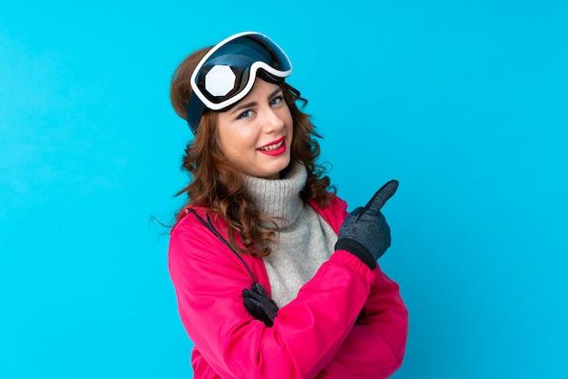 Donna dello sciatore con i vetri di snowboard sopra la parete isolata