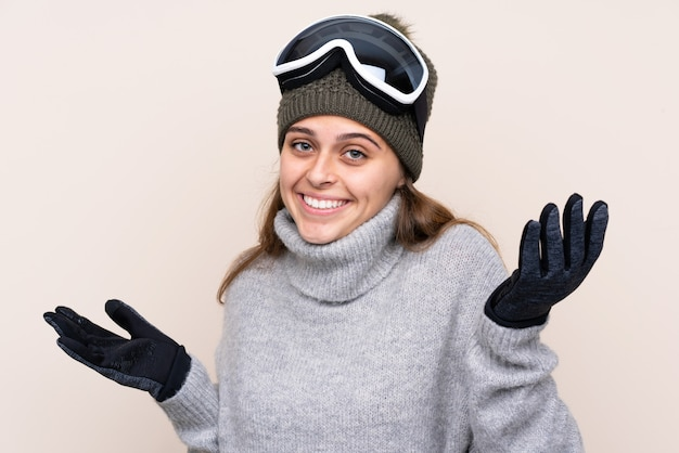 Donna dello sciatore dell'adolescente con i vetri di snowboard sopra la parete isolata con espressione facciale colpita