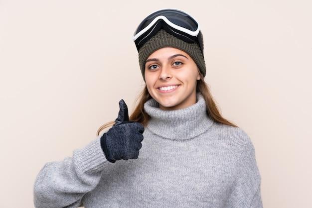 Donna dello sciatore dell'adolescente con i vetri di snowboard sopra la parete isolata con i pollici su perché è successo qualcosa di buono