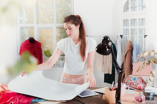 Donna dello stilista che lavora nello studio che si siede sullo scrittorio