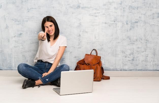 Donna dello studente che si siede sul pavimento che mostra e che solleva un dito
