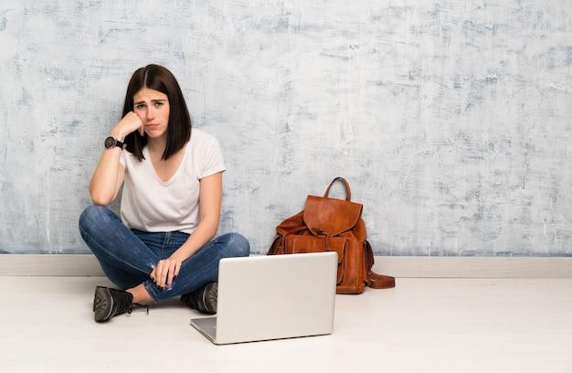 Donna dello studente che si siede sul pavimento con l'espressione triste e depressa