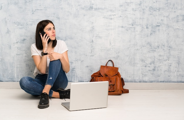 Donna dello studente che si siede sul pavimento mantenendo una conversazione con il telefono cellulare