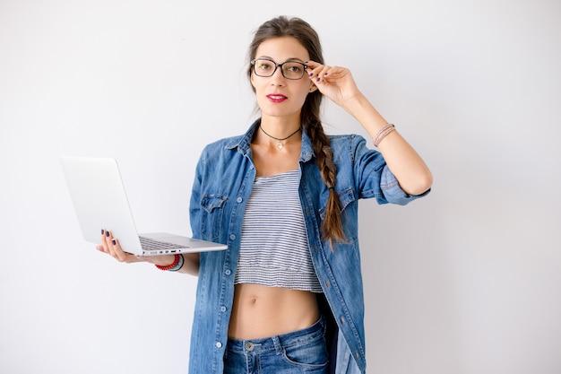 Donna dello studente che sta con un computer portatile in sue mani